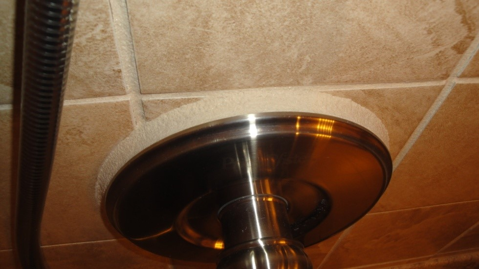 "The image below shows the shower valve protruding from the wall tile which the tile ""placer"" filled in with grout."