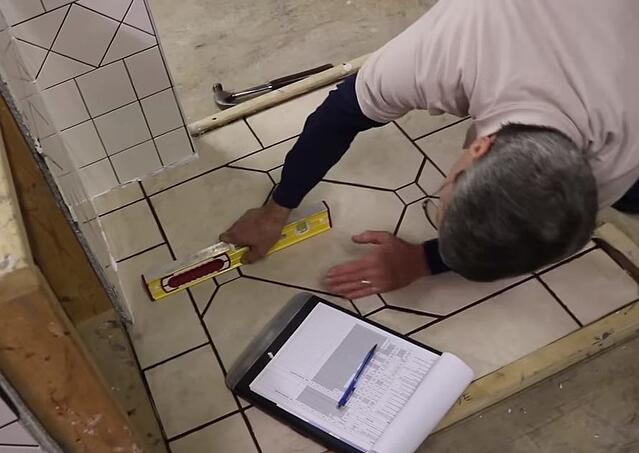 Scott checks the insert dots in the floor to make sure that they are flush with the floor tile both left and right and north and south.