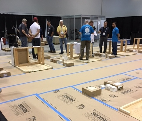 The mock-up consists of a bare wooden frame where the future CTImust install a backer board on the walls and floor as well as tile of different sizes installed in a pattern with a border according to the test parameters