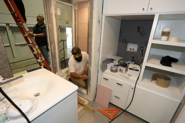 Experts from Visalia Ceramic Tile installing tile in the Retro Bungalow Tiny Home Bathroom
