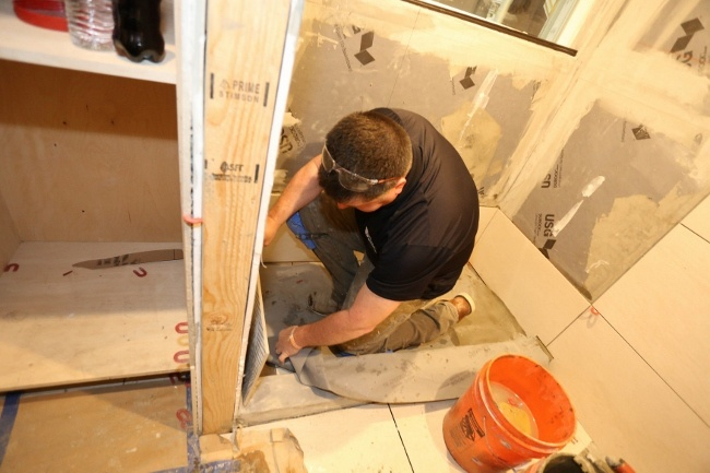 Welch Tile and Marble working on the shower in a tiled tiny house