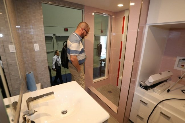Coverings17 visitor admiring the tile work in the Retro Bingalow Tiny House bathroom