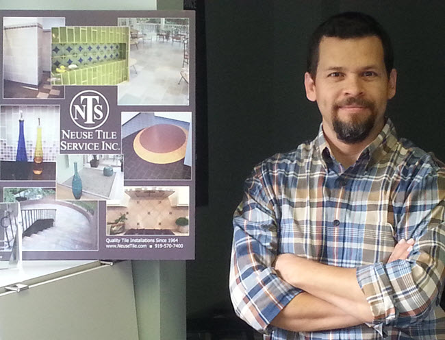 Neuse Tile Service's Juan Sauceda CTI#64, with a poster depicting many projects that he has either overseen or installed.