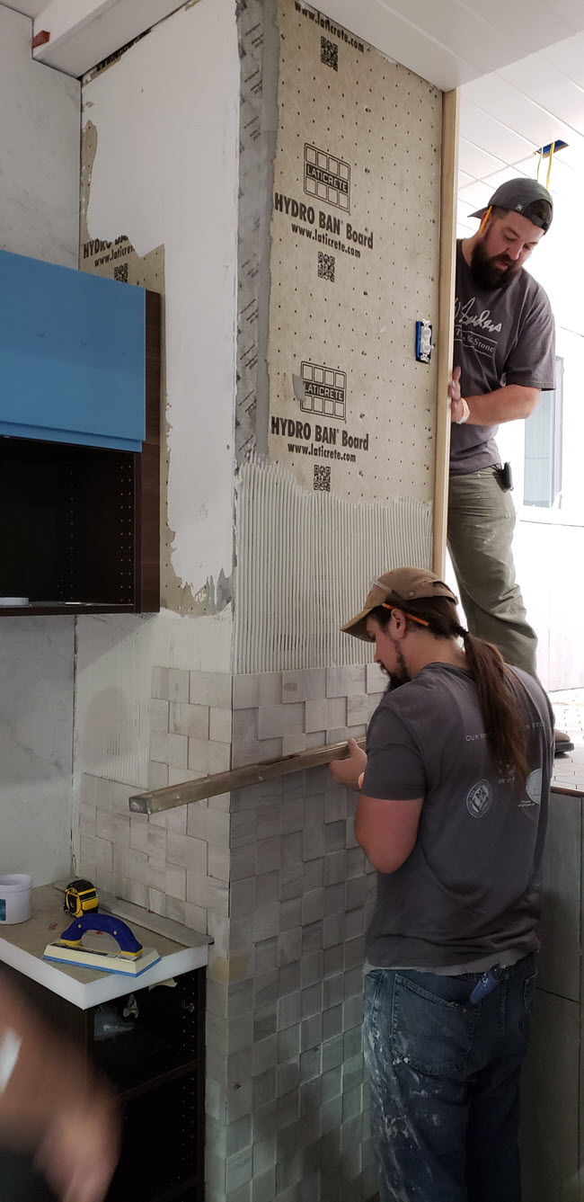DW Sanders installing tile in a tiny home at Coverings 18